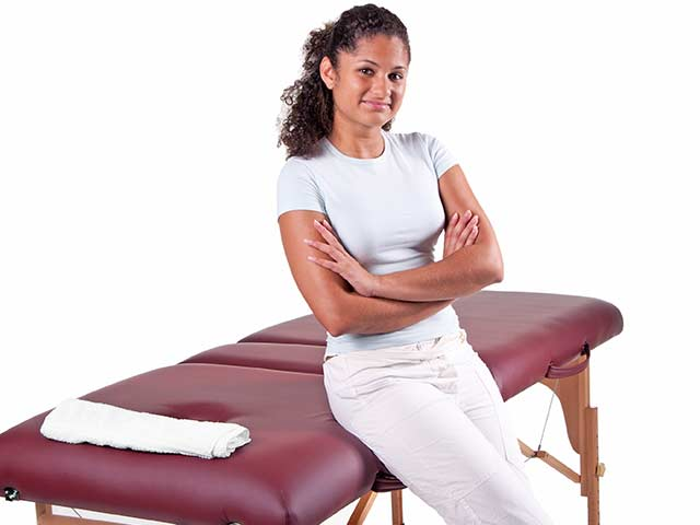 female masseuse leans against a massage table