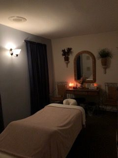 Healing Hands Massage therapy room with soft glowing light and a heated massage table in West Chester, PA